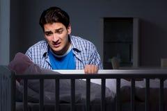 在重音下的年轻父亲由于哭泣在晚上的婴孩 库存图片