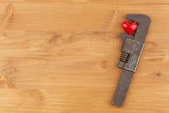 在重音下的心脏 生锈的恶习被击碎的红色心脏 在工作之下的重点 免版税库存图片