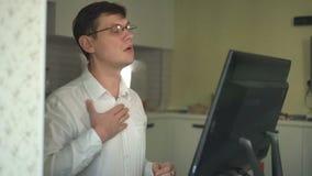 在重音期间,一个人解扣在一件白色衬衣的一个按钮在一个闷家庭办公室 影视素材