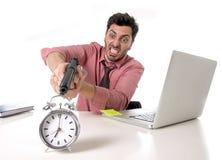 在重音的商人在办公计算机书桌指向手枪的闹钟在的时间和到期的工程截止期限外面 免版税库存图片