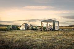 在野营假日期间,在夏天领域日落天空的露营地野营的帐篷 免版税图库摄影