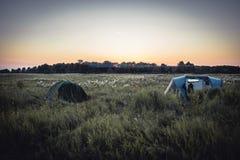 在野营假日期间,有野营的帐篷的露营地在夏天农村领域和日落天空 库存照片
