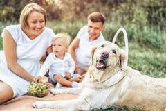 在野餐的年轻逗人喜爱的家庭与狗 免版税库存照片