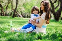 在野餐的愉快的家庭为母亲节 吃甜点的妈妈和小孩儿子室外在春天或夏天 免版税库存照片