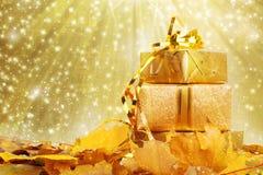 在金包装纸的礼物盒与秋叶 库存图片