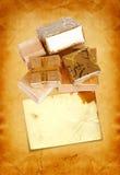 在金包装纸的礼物盒在纸板背景 库存照片