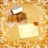 在金包装纸的礼物盒在葡萄酒纸板背景 库存图片