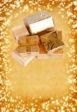 在金包装纸的礼物盒在葡萄酒纸板背景 免版税库存图片