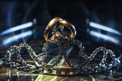 在金子做的不同的大小两个婚戒在冠状头饰 免版税库存照片