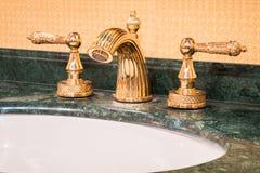 在金子的减速火箭的龙头 豪华龙头搅拌器在一个美丽的卫生间里 库存照片