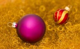 在金子的紫色和红色圣诞节球闪烁 库存照片