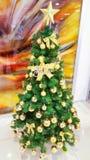 在金子装饰的圣诞树和圣诞节装饰品和金子在上面担任主角 免版税库存图片