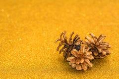 在金子闪烁背景的三个金黄锥体 欢乐的装饰 免版税库存图片