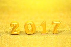在金子闪烁背景,新年好概念的2017个真正的3d对象 免版税库存照片