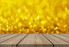 在金子闪烁bokeh摘要backgroundd的木地板 免版税图库摄影