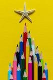 在金字塔计划的色的铅笔 在铅笔海星顶部 在黄色纸背景 图库摄影