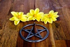 在金属五角星形的灼烧的香火与黄色大丽花开花  免版税图库摄影