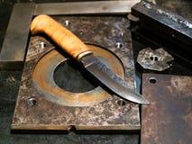 在金属工作凳的伪造的刀子 库存图片