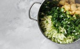 在金属平底深锅的切好的汤产品 免版税库存照片
