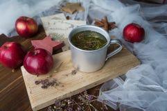在金属杯子和红色苹果的清凉茶 库存图片
