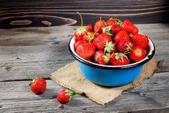 在金属杯子的红色莓果草莓在土气木背景 免版税库存照片