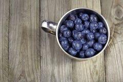 在金属杯子的蓝莓在木背景或纹理 免版税库存图片