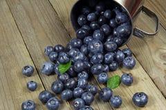 在金属杯子的蓝莓在木背景 库存照片