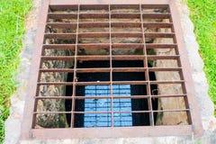 在金属格栅下的排水管 库存图片