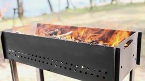 在金属格栅火盆的美好的橙色火 在火盆的木燃烧在明亮的黄色火 火焰厨师的火准备 股票录像