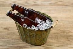 在金属桶的冰镇啤酒瓶用冰填装了 免版税库存图片
