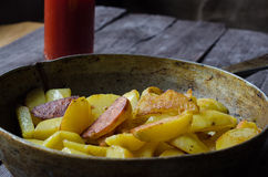 在金属煎锅特写镜头的新鲜的开胃烤土豆片 库存图片