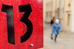 在金属片的红色的第十三标志 免版税图库摄影