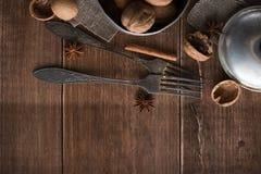 在金属的核桃滚保龄球,黑暗的背景 核桃壳和桂香在木桌上 免版税库存图片