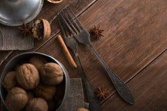 在金属的核桃滚保龄球,黑暗的背景 核桃壳和桂香在木桌上 免版税库存照片