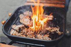 在金属的格栅牛排磨碎与火焰,烤肉 免版税库存照片