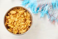 在金属的玉米片在被绘的白色木背景滚保龄球 与洗碗巾的构成 免版税库存图片