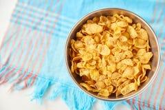 在金属的玉米片在被绘的白色木背景滚保龄球 与洗碗巾的构成 图库摄影