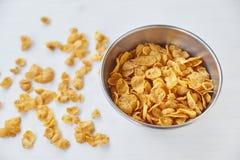 在金属的玉米片在被绘的白色木背景滚保龄球 在一张木桌上驱散的玉米片 免版税图库摄影