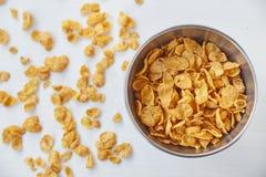 在金属的玉米片在被绘的白色木背景滚保龄球 在一张木桌上驱散的玉米片 免版税库存图片