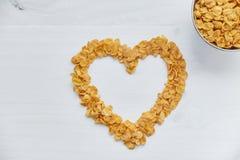 在金属的玉米片在被绘的白色木背景滚保龄球 心脏的标志被计划玉米片 免版税图库摄影