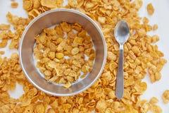 在金属的玉米片滚保龄球用在被绘的白色木背景的牛奶 在一张木桌上驱散的玉米片与 免版税图库摄影