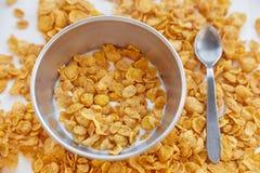 在金属的玉米片滚保龄球用在被绘的白色木背景的牛奶 玉米片在与匙子的一张木桌上驱散了 免版税库存照片