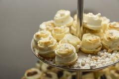 在金属盘子的乳脂状的花卉形状的甜点心 库存照片