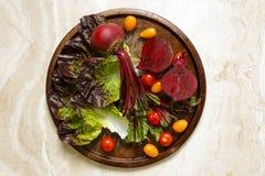 在金属盘子的新鲜的甜菜根以西红柿和宝石莴苣品种  免版税库存图片