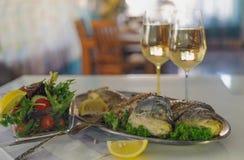 在金属盘的油煎的在白色桌上的鱼与绿色和柠檬 户内 免版税库存图片