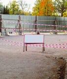 在金属篱芭附近之外倒空在一个木广告牌的白色空间在 免版税库存照片