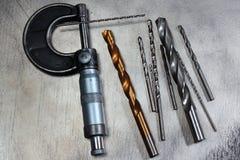 在金属背景的钻头和千分丝杠轮尺 免版税库存图片