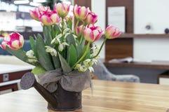 在金属花盆的桃红色郁金香在一张木桌上 免版税库存图片