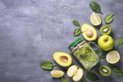 在金属螺盖玻璃瓶和成份的健康绿色圆滑的人 免版税库存图片