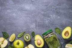 在金属螺盖玻璃瓶和成份的健康绿色圆滑的人 免版税库存照片